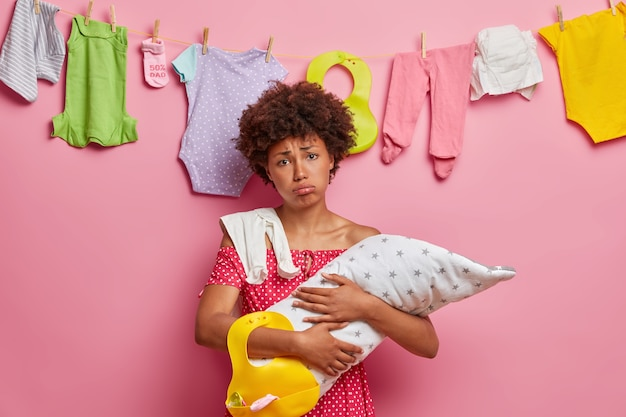 Depressieve, vermoeide moeder geeft om baby, heeft slapeloze nachten en veel huishoudelijk werk, heeft een dutje nodig, probeert een huilende baby glad te strijken, uitgeput van de verpleging, bezig met huishoudelijke klusjes, wast kinderkleding