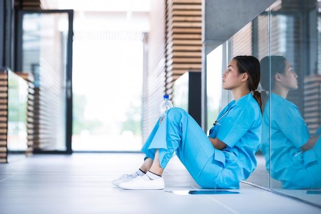Depressieve verpleegster zittend op de vloer