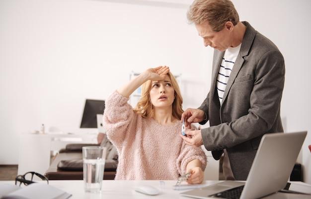 Depressieve verzwakte jonge vrouw die in het zakencentrum zit en verkouden is terwijl ze hulp krijgt van een volwassen collega Premium Foto