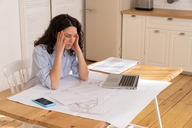 Depressieve vrouw externe werknemer met hoofdpijn die op laptop werkt vanuit huis