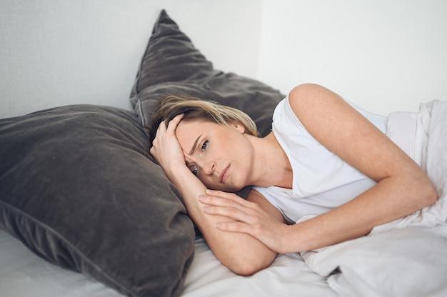 Depressieve vrouw gekweld door rusteloze slaap, is uitgeput en lijdt aan slapeloosheid, nare dromen of nachtmerries, psychische problemen. ongemakkelijk ongemakkelijk bed of matras. slaapgebrek