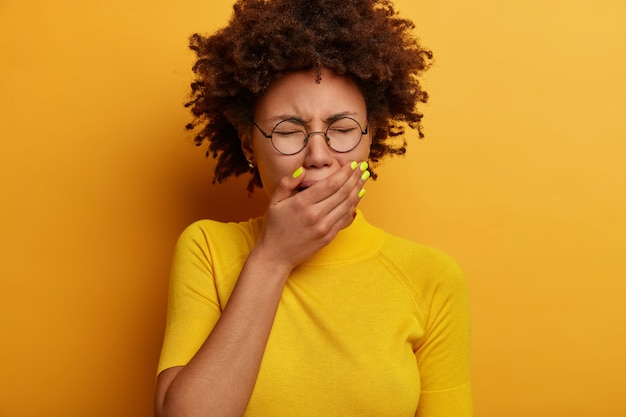 Depressieve vrouw met een donkere huid huilt van wanhoop, bedekt de mond, ziet er ellendig uit, jankt luid, draagt een optische bril, een geel casual t-shirt, poseert binnenshuis, moe van problemen. negatieve emoties
