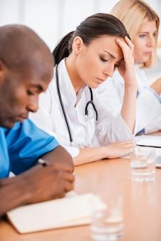 Depressieve vrouwelijke arts. depressieve jonge vrouwelijke arts die de hand in het haar houdt terwijl ze samen met haar collega's op de vergadering zit
