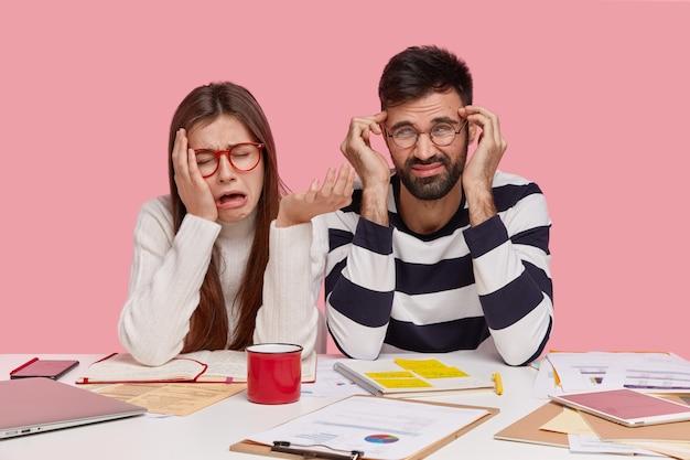 Depressieve vrouwelijke en mannelijke groepsgenoten zien er ongelukkig uit, uiten negatieve gevoelens, zitten samen op de werkplek