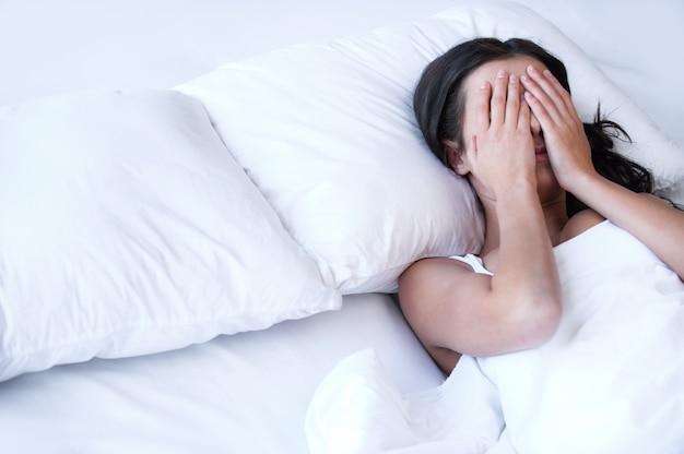 Depressieve vrouwen in bed. bovenaanzicht van jonge trieste vrouwen die op het bed liggen en haar gezicht in handen verbergen