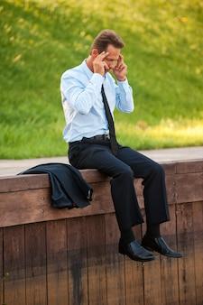 Depressieve zakenman. depressieve volwassen zakenman die zijn hoofd in handen houdt terwijl hij aan de kade zit