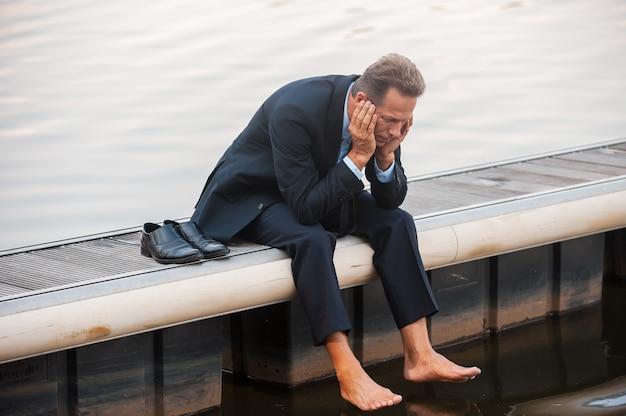 Depressieve zakenman. depressieve volwassen zakenman die zijn hoofd in handen houdt terwijl hij op blote voeten aan de kade zit