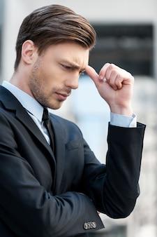 Depressieve zakenman. zijaanzicht van depressieve jongeman in overhemd en stropdas die wegkijkt