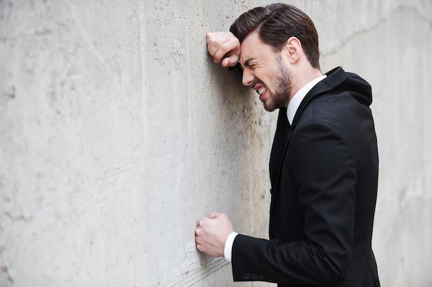 Depressieve zakenman. zijaanzicht van een depressieve jongeman in overhemd en stropdas die tegen de muur leunt en zijn ogen gesloten houdt