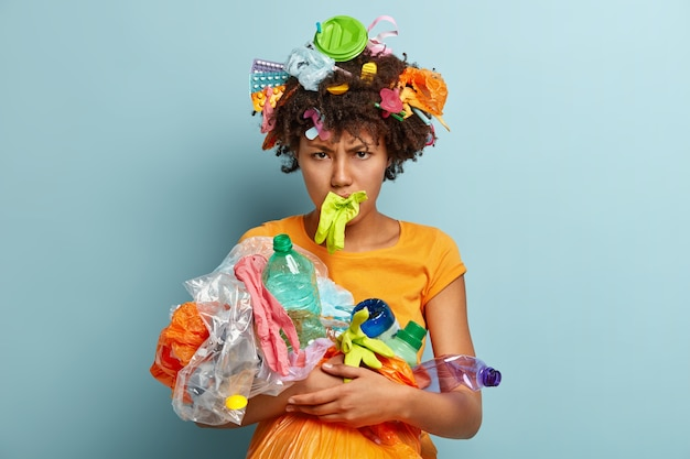 Depressieve zwarte vrouw met knapperig haar, pakt vuilnis op, heeft negatieve gezichtsuitdrukking geïrriteerd, reinigt omgeving geïsoleerd over blauwe muur, sorteert afval. mensen, recycling, vrijwilligerswerk concept