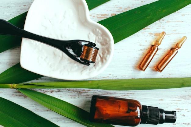 Dermaroller en serum naast een anti-aging gezichtscrème schoonheidsindustrie close-up dermaroller voor medische micronaaldbehandeling