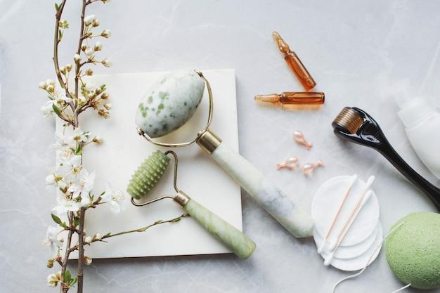 Dermaroller en serum naast een anti-aging gezichtscrème schoonheidsindustrie dermaroller voor medische micro-naaldbehandeling derma-rolmesoroller voor mesotherapie bij bloemen
