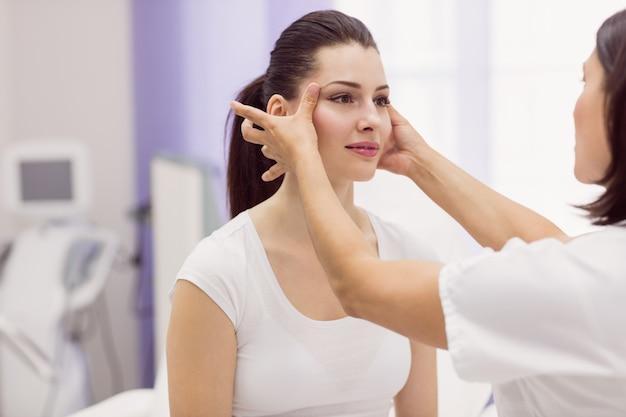 Dermatoloog die de huid van de vrouwelijke patiënt onderzoekt