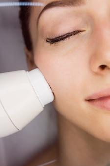 Dermatoloog die gezichtsmassage geeft door sonic lifting