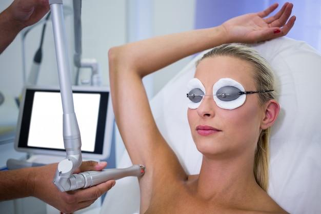 Dermatoloog die haar van de oksel van de patiënt verwijdert