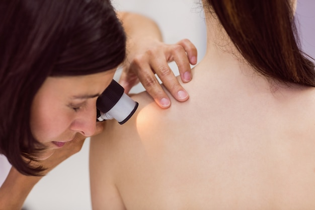 Dermatoloog die huid van patiënt met dermatoscope onderzoekt