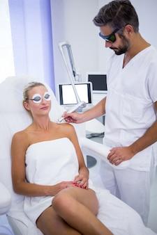 Dermatoloog die mol van de schouder van de vrouw verwijdert