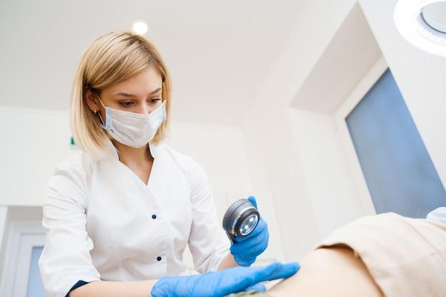 Dermatoloog maakt een onderzoek met een dermatoscoop. overleg met een arts. verjongingsprocedure