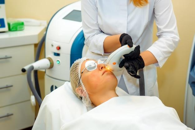 Dermatoloog met laserapparaat maakt gezichtsverjongingsprocedure voor een vrouw die in het kantoor van een cosmetologiekliniek ligt