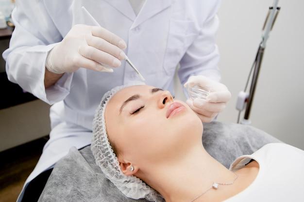 Dermatoloog zet een voedingsmasker op de jonge en mooie vrouwenhuid na het schoonmaken om haar huid glad en gezond te maken.