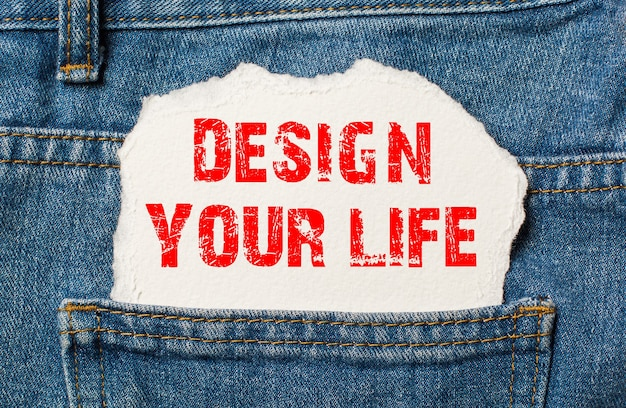 Design your life op wit papier in de zak van een blauwe spijkerbroek