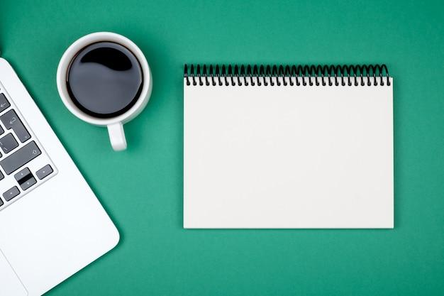 Designer bureau met lege notebook pagina en laptop