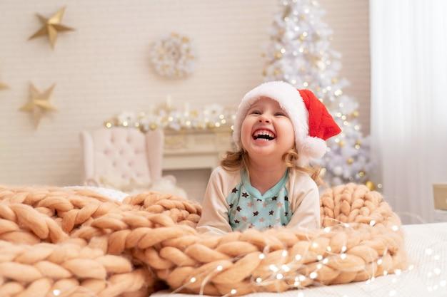 Designer dekens van merino beige! lachend kind in kerstmuts. achter het meisje op de achtergrond staat een kerstboom bij het raam. gelukkig kind liggend op het bed vreugde bij het begin van kerstmis
