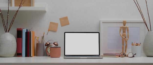 Designer huis met een laptop, boeken en decoraties op witte tafel