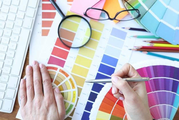 Designer ontwikkelt kleurencombinaties op desktop. kleuroplossingen in het interieurconcept
