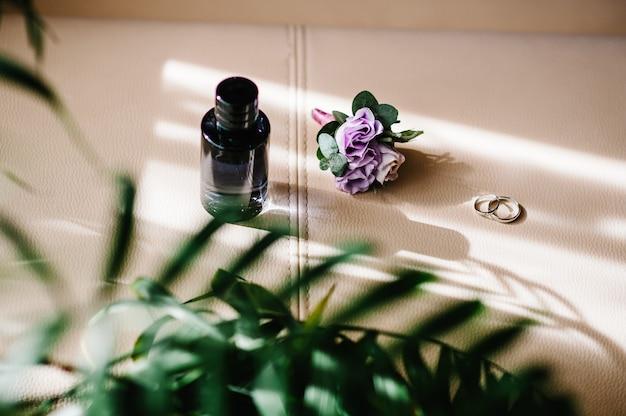 Designer silver twee trouwringen, parfumfles en bloemen op een beige achtergrond met kopieerruimte. verloving. luxe huwelijk en bruiloft accessoire concept.