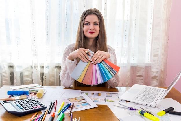 Designer vrouw die werkt met kleurstalen, werkplek