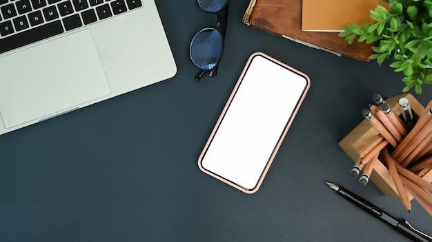 Designer werkruimte met smartphone, laptop, potloodhouder en notitieboekje op zwart leer.