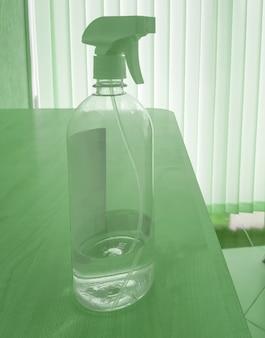 Desinfecterende fles alcohol spray verspreidende antibacteriële ontsmettingsmiddel dat de verspreiding van ziektekiemen, bacteriën, virussen op het bureau op kantoor voorkomt.