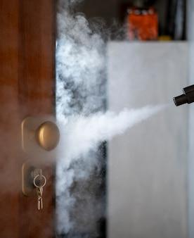Desinfectie en ontsmetting met stoom thuis, stoomstroom wordt naar de deurkruk en sleutels in het slot geleid