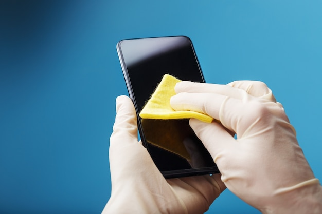 Desinfectie van de smartphone met een geel servet met antibacteriële impregnering in handhandschoenen