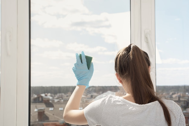 Desinfectie van gebouwen, algemene reiniging. jong meisje in handschoenen wast een raam met een spons