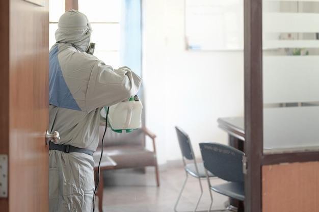 Desinfectie van kantoor om covid-19 te voorkomen, persoon in wit hazmatpak met desinfectie op kantoor, coronavirusconcept