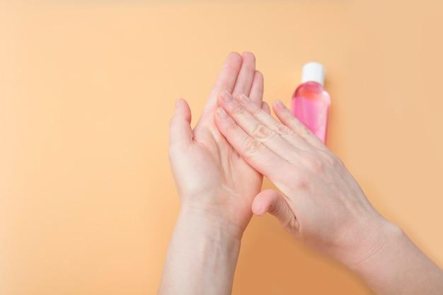 Desinfectie van vrouwelijke handen met ontsmettingsgel tegen virus en bacteriën op oranje achtergrond. coronavirus bescherming en gezondheidszorg concept. veiligheidsregels tijdens quarantaine. kopieer ruimte voor tekst