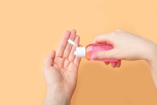 Desinfectie van vrouwelijke handen met ontsmettingsgel tegen virus en bacteriën op oranje achtergrond. coronavirus bescherming en gezondheidszorg concept.