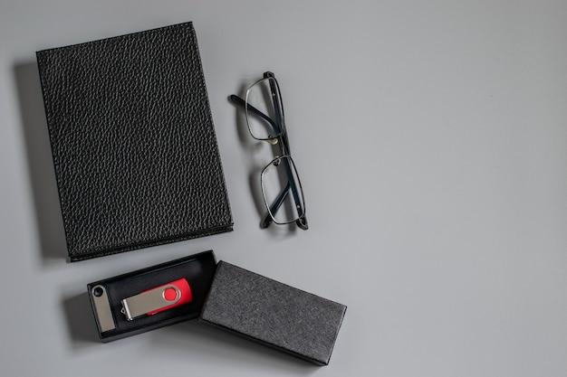Desktop met fotoalbum, ogenbril en usb-flitsapparaat, ontwerp op grijze achtergrond. mockupfoto met ruimte voor uw tekst.