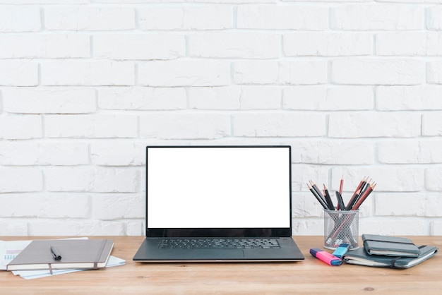 Desktop met laptop en kantoorelementen
