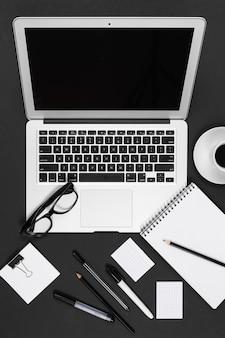 Desktop met laptop, koptelefoon, rekenmachine, pennen, potloden, kaart, telefoon geïsoleerd op zwart-witte achtergrond