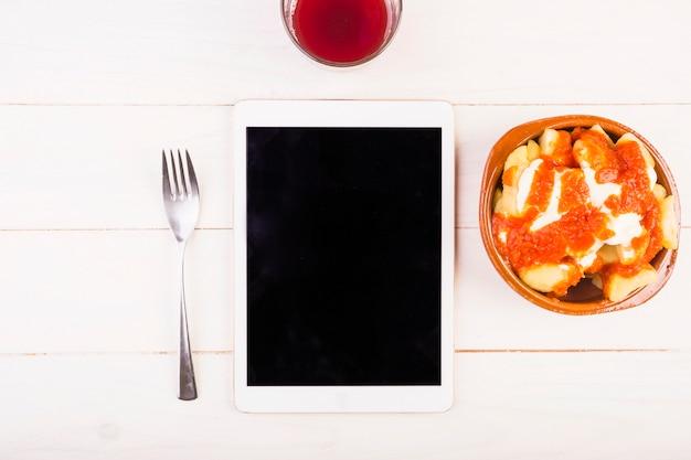 Desktop met tablet en voedselplaat