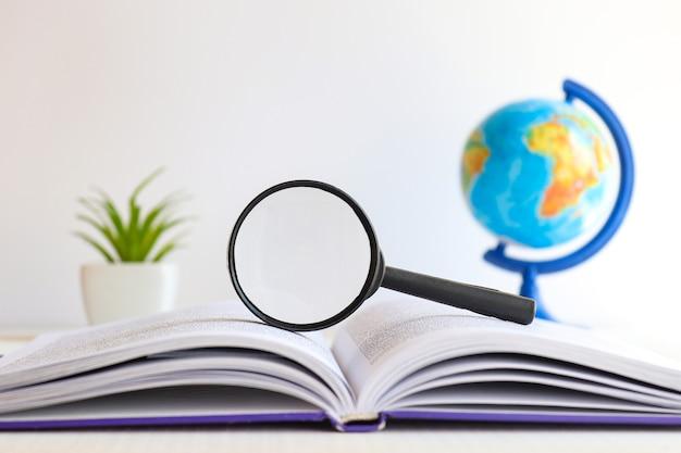 Desktop met vergrootglas boekbol en plant kopieerruimte selectieve focus onderwijs en zaken