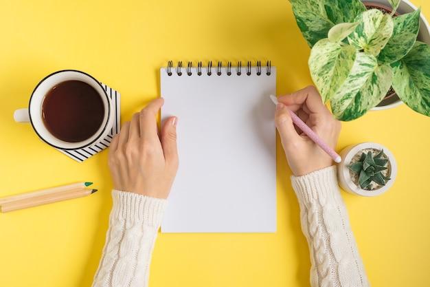 Desktop van vrouwenhanden die in lege blocnote schrijven