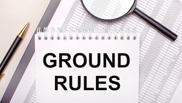 Desktop vergrootglas, rapporten, pen en notitieboekje met tekst ground rules. bedrijfsconcept