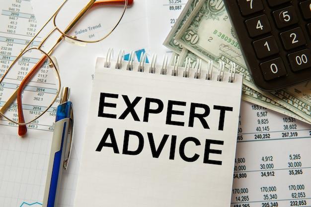 Deskundig advies is geschreven op een notitieblok, op een bureau met kantooraccessoires.