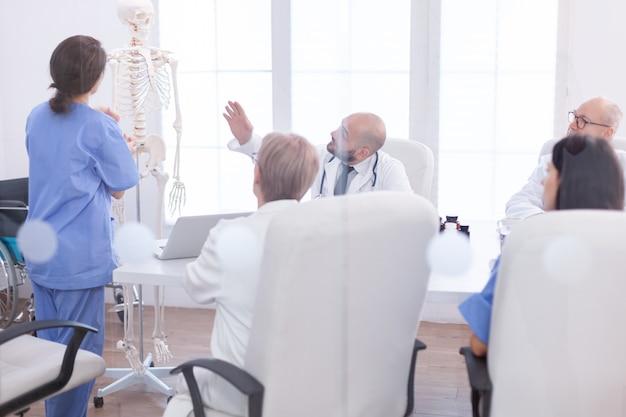 Deskundige arts in de radiologie wijzend op het menselijk skelet tijdens de presentatie in de vergaderruimte van het ziekenhuis. kliniektherapeut in gesprek met collega's over ziekte, medische professional.