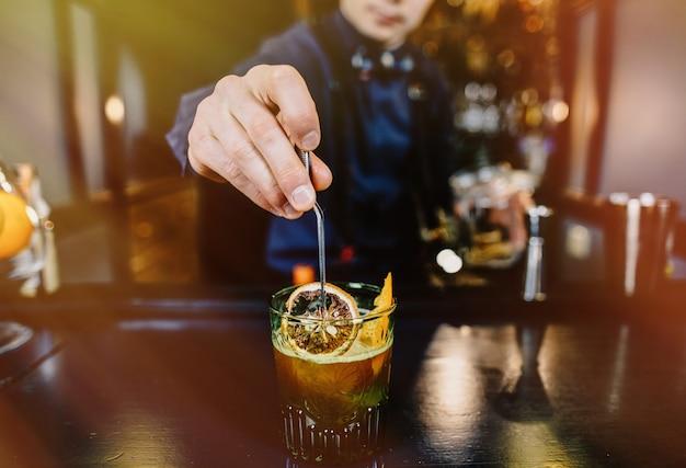 Deskundige barman die cocktail maakt bij bar
