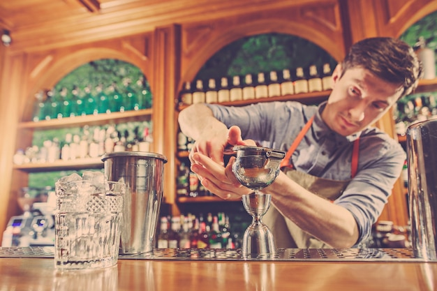 Deskundige barman maakt cocktail in nachtclub of bar.